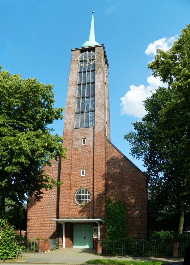 Die Kirche umrahm von Bäumen vor blauem Himmel.