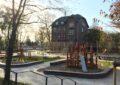 Ein neugebauter Spielplatz und Treffpunkt für das Viertel Georgswerder. Im Vordergrund ist ein Spielgerät mit Rutsche, im Hintergrund das historische Schulgebäude aus Backstein. Links im Bild sind Bäume und Sonnenlicht zu sehen.