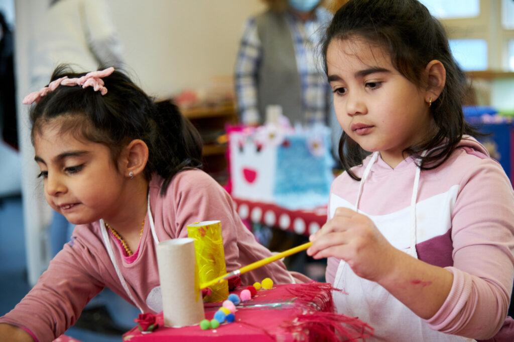 Zwei Mädchen im Vorschulalter basteln konzentriert an einer Maske aus Pappkarton. Die Maske ist mit zwei Klopapierrollen beklebt, die von einem Mädchen gerade gelb angepinselt werden. Die Kinder tragen weiße Schürzen beim Basteln.