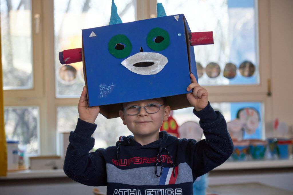 Ein Junge im Vorschulalter guckt mit einem stolzen Grinsen unter einer blauen Pappkarton-Maske hervor. Seine Maske hat grüne Augenschlitze, einen weißen Mund und rote Ohren aus Klopapierrollen.