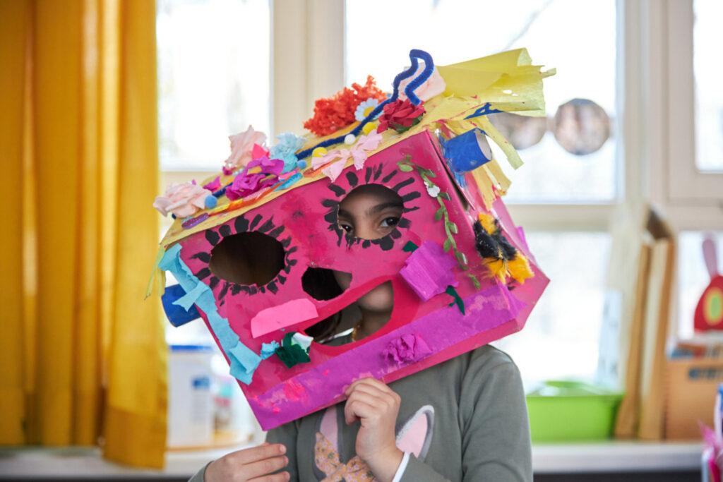 Eine Vorschülerin, die ihre rosane, bunt beklebte Pappkarton-Maske aufgesetzt hat und durch die ausgeschnittenen Augen guckt.
