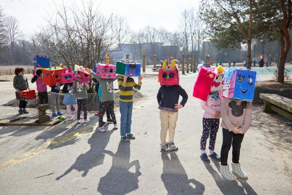 Zehn Grundschulkinder bilden eine Schlange auf einem sonnenbeschienenen Schulhof. Sie haben selbstgebastelte Masken aus Pappkartons über ihre Köpfe gestülpt. Die Masken sind bunt, wild, fantasievoll und jede ist anders. Sie haben alle Augen und Mund und sind oben drauf mit allerlei Deko geschmückt.