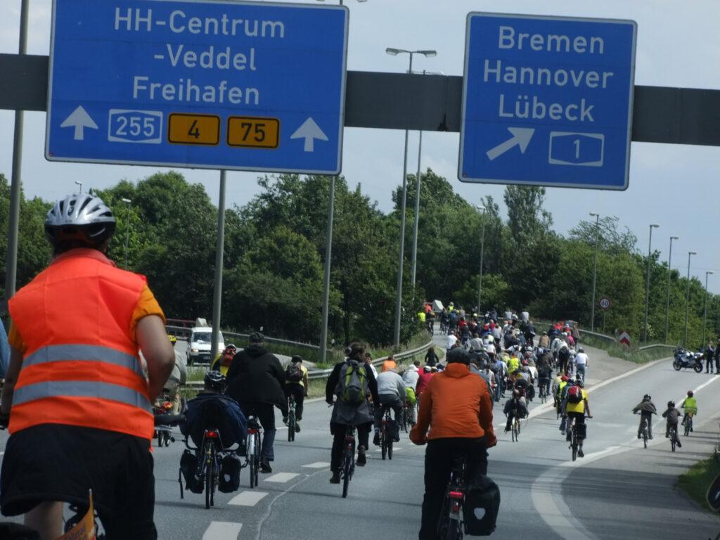 Ein großer Pulk Fahrradfahrer:innen, Alt und Jung, mit bunten Helmen und Jacken, fährt über eine Autobahn. Die Radler:innen sind von hinten aufgenommen.