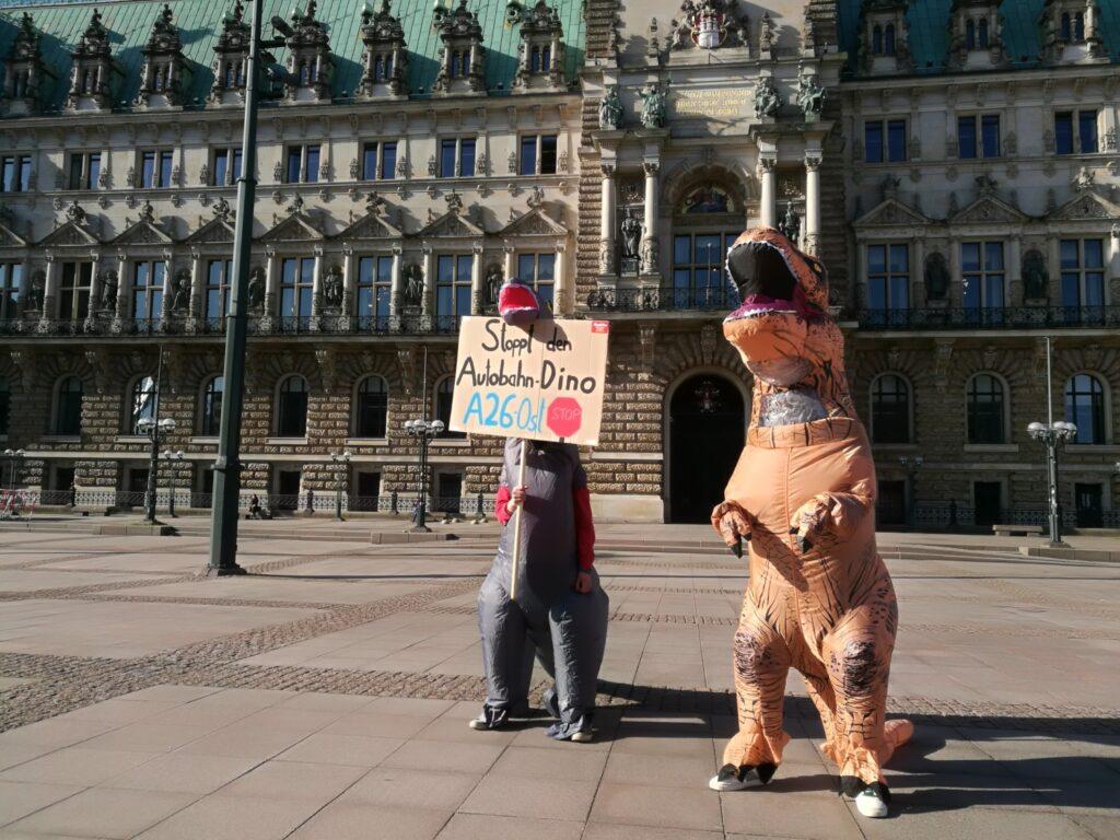 """Auf dem Platz vor dem Hamburger Rathaus stehen zwei als Dinosaurier verkleidete Personen. Einer hält ein Schild hoch, auf dem steht: """"Stoppt den Autobahn-Dino A26 Ost!"""""""