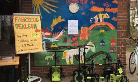 Eingang zum Spielhaus mit bunter Wandbemalung und Flipchart zum Ausleihangebot