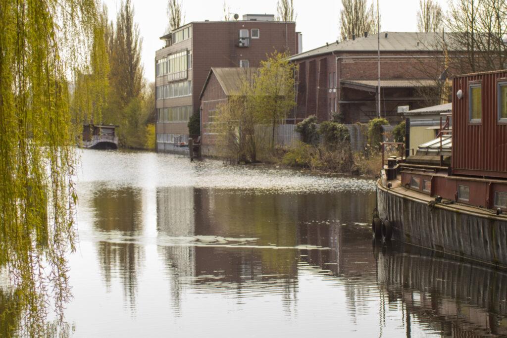 Ein Kanal, spiegelnde Wasseroberfläche, links ragt eine Trauerweide ins Bild, rechts sieht man das Heck einer Schute und Gewerbegebäude. Es handelt sich um den Veringkanal.
