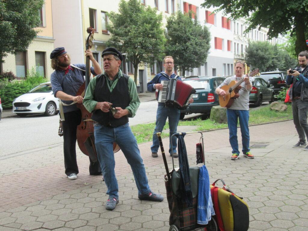 Auf dem Bild geben drei Musiker mit Bass, Akkordeon und Gitarre und ein Sänger ein kleines Konzert auf einer Straße in Georgswerder.