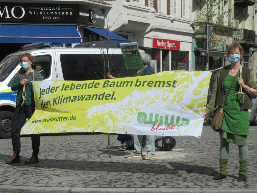 """Zwei Frauen halten auf einer belebten Kreuzung ein Transparent, auf dem steht: """"Jeder lebende Baum bremst den Klimawandel"""" und """"WiWa bleibt!"""" Im Hintergund sieht man zwei Ladenschilder """"Eiscafé Wilhelmsburg"""" und """"Vering Sport."""""""