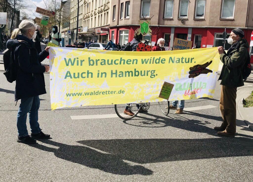 """Eine Frau und ein Mann halten auf einer belebten Kreuzung ein Transparent, auf dem steht: """"Wir brauchen wilde Natur. Auch in Hamburg."""" und """"WiWa bleibt!"""". Im Hintergund sieht man weitere Schilder und Plakate zum Thema """"Walderhalt"""""""