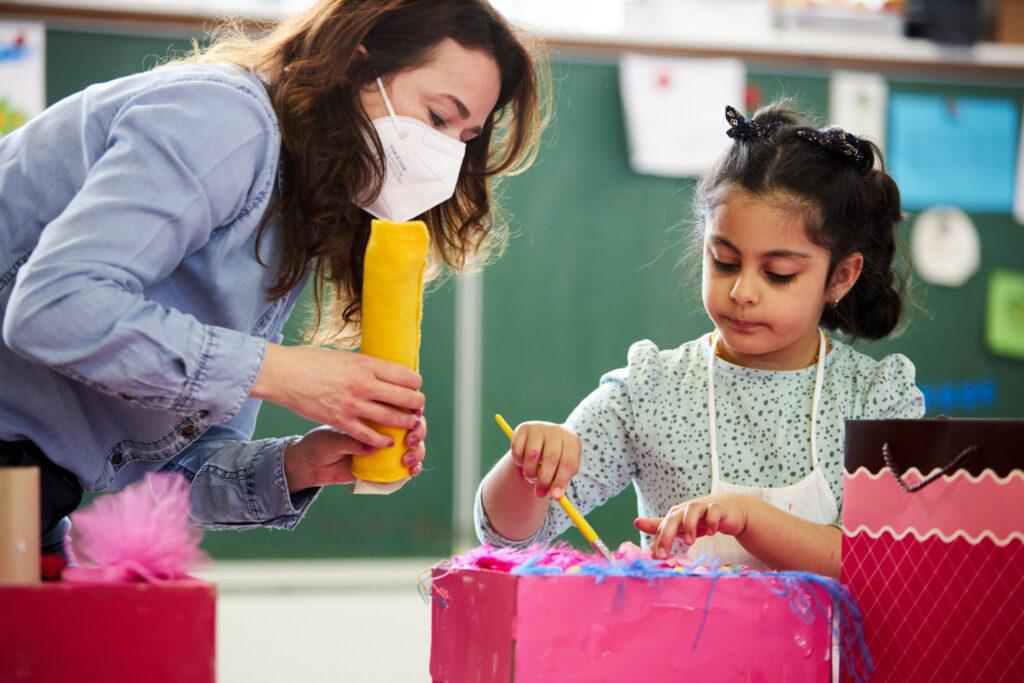 Eine Frau hilft einer Vorschülerin beim Basteln einer Maske aus einem Pappkarton. Der Pappkarton des Mädchens ist rosa angemalt und mit bunten Federn beklebt. Das Mädchen hantiert mit einem Pinsel, während die Frau ihr eine gelbe Filzrolle reicht. Das Foto ist in einem Klassenzimmer aufgenommen, im Hintergrund sieht man eine Tafel.