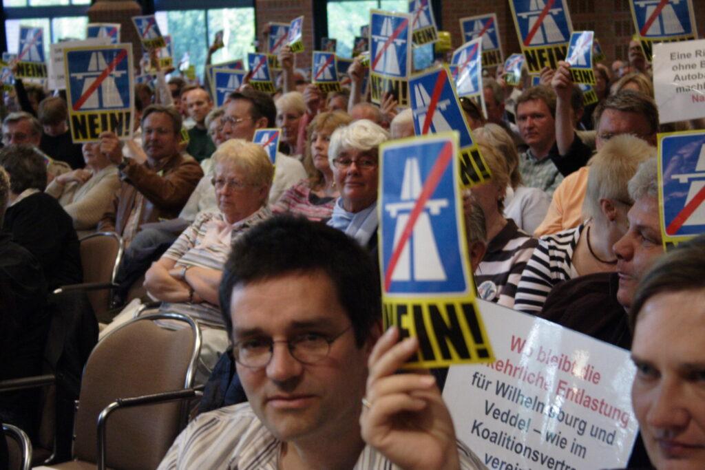 """Die Stuhlreihen eines Veranstaltungssaals sind dicht besetzt mit Menschen, ein großes Publikum. Viele der Menschen halten ein Schild hoch, darauf ist eine durchgestrichene Autobahn abgebildet, unten steht in Großbuchstaben """"NEIN!"""". Es ist ein Schilderwald in diesem Publikum."""