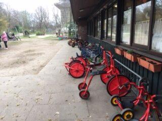 Vor dem Spielhaus. Rechts davor einige Fahrgeräte wie Hochräder und Roller. Im Hintergrund der Park und Spielplatz.