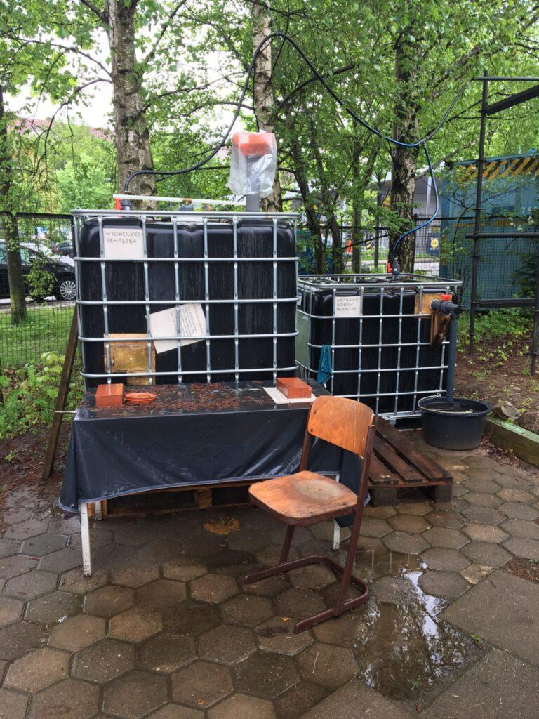 Frontalansicht Biogasanlage, zwei schwarze Container mit Gittergehäuse. Aufgestellt draußen auf einem Tisch, vor der Anlage ein Stuhl. Einfülltrichter für Bioabfälle auf dem Container.
