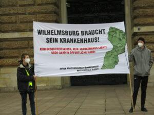Zwei Demonstranten stehen vor dem Rathaus mit einem Transparent: Wilhelmsburg braucht sein Krankenhaus