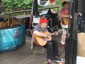 Zwei Musiker mit Gitarre singen nd spielen auf dem Floß Schaluppe