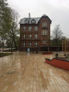 Frontalansicht des Schulgebäude, dem Künstlerhaus in Georgswerder. Sicht vom Quartiersplatz, links ein Baum, rechts Sitzbänke.
