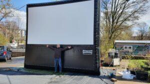 Auf dem Bild ist eine große aufblasbare Kinoleinwand auf dem Hof der Honigfabrik zu sehen.