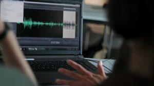 PC-Bildschirm in Schwarz links im Bild. Audio-Rekord zu sehen. Im Vordergrund eine schemenhafte Person.