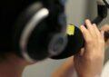 Vordergrund: schemenhafter Kopf mit Kopfhörern, ein Mikrofon in der Hand im Bildhintergrund