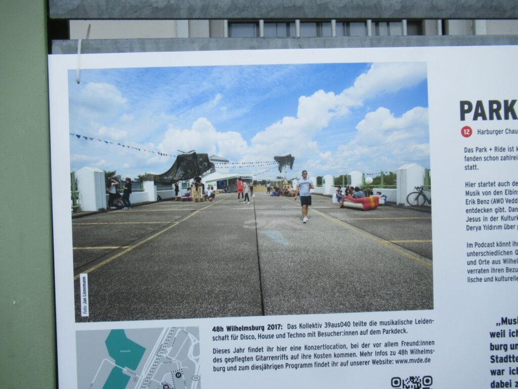 Das Foto zeigt das Parkdeck am S-Bahnhof Veddel, mit Fähnchen für die 48 Stunden geschmückt. Einige Menschen gehen herum oder sitzen in den improvisierten Sitzgruppen.