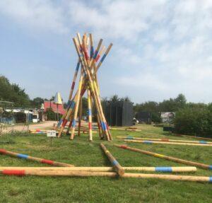 Ein riesiges Mikadospiel aus verschiedenen Holzarten und mit typischer Bemalung. Ein Teil der Spielstangen steht noch, andere liegen im Gras.
