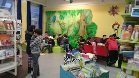 Das Bild zeigt die jetzige Stadtteilbücherei Veddel mit Bücherregalen und einer Gruppe Jugendlicher beim Lernen.