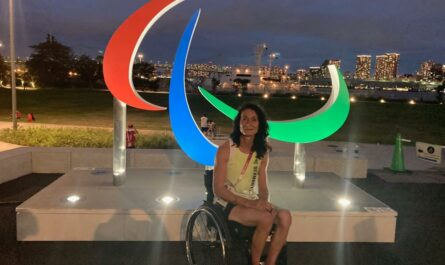 Sylvia-Pille-Steppat in Tokio vor dem Symbol der Paralympics und der abendlichen Silhouette der Stadt.