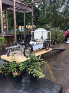 Lastenfahrrad auf Podest, mit Behälter um Bioabfälle zu transportieren.