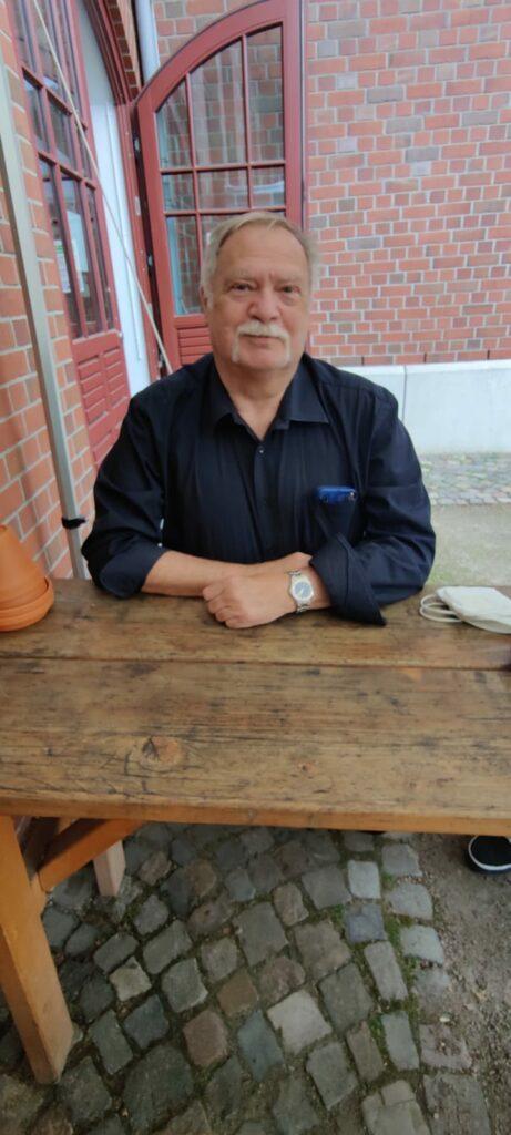 Dieter Thal, ein verhalten lächelnder Mann mit Schnauzbart, an einem Holztisch im Innenhof der Ballinstadt.