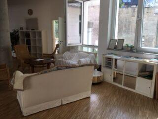 Innenraum mit Holzboden, weiße Sofarücklehne in der Bildmitte, dahinter ein Korbsessel. Rechts ein weißes Regal. Ein geöffnetes Fenster im Hintergrund.