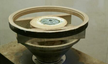 Das Bild zeigt eine Skulptur aus der Kunsthalle, sie ist rund mit einem Messgerät in der Mitte, wie eine Schale in hell oliv, das Material ist nicht bekannt.