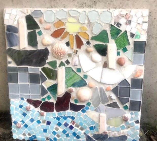 Ein buntes, fröhliches Mosaik mit ganz vielen Formen, z. B. ein Segelboot, eine Sonne, eine Windmühle. Dazwischen einige Muscheln.